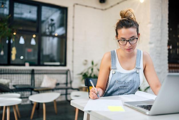 Jeune femme prendre des notes et étudier avec un ordinateur portable dans un lieu public.