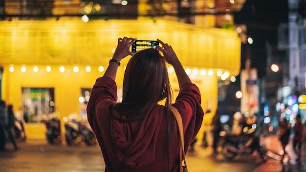 Jeune femme prendre une photo par téléphone intelligent et voyager dans la ville de nuit à dalat vietnam