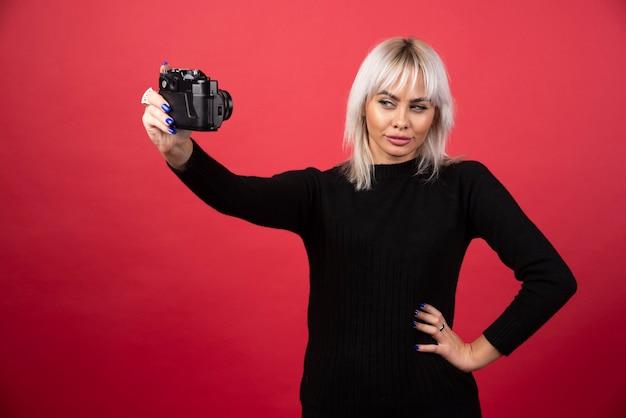 Jeune femme à prendre des photos avec un appareil photo sur fond rouge. photo de haute qualité