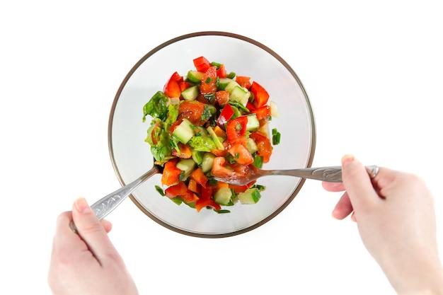 Jeune femme préparant une salade de légumes sains. salade fraîche avec légumes tomates, concombres, laitue, feuilles de salade sur fond blanc vue de dessus.