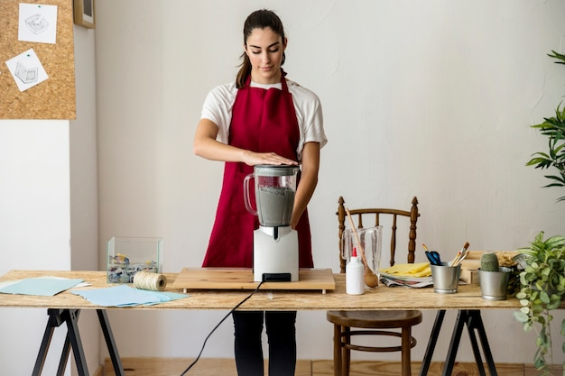 Jeune femme, préparation, pâte papier, dans, mélangeur, à, atelier