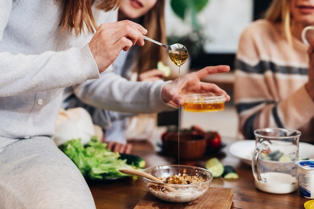Une jeune femme prépare un repas, ajoute du miel au granola.