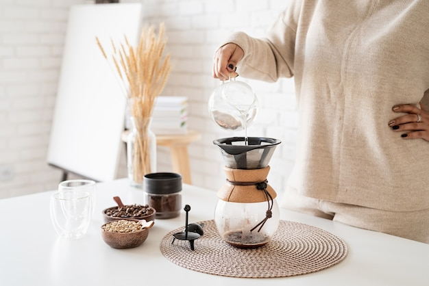 Jeune femme, préparer, café, dans, cafetière, verser, eau chaude