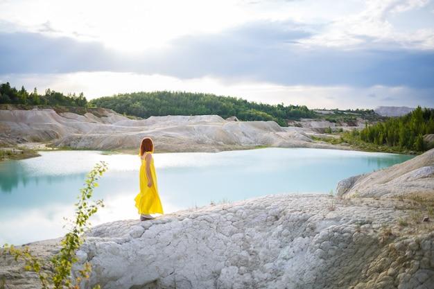 Jeune femme près d'un lac avec de l'eau azur et des montagnes pierreuses avec des arbres verts. belle vue sur le lac dans la forêt