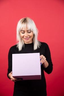 Jeune femme avec présent sur fond rouge. photo de haute qualité