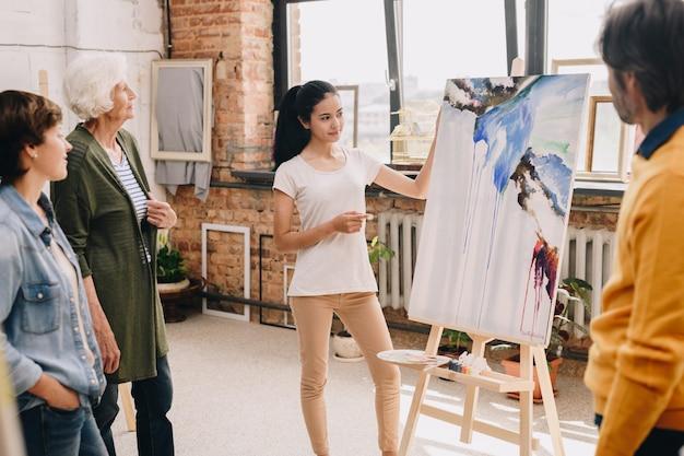 Jeune femme présentant la peinture