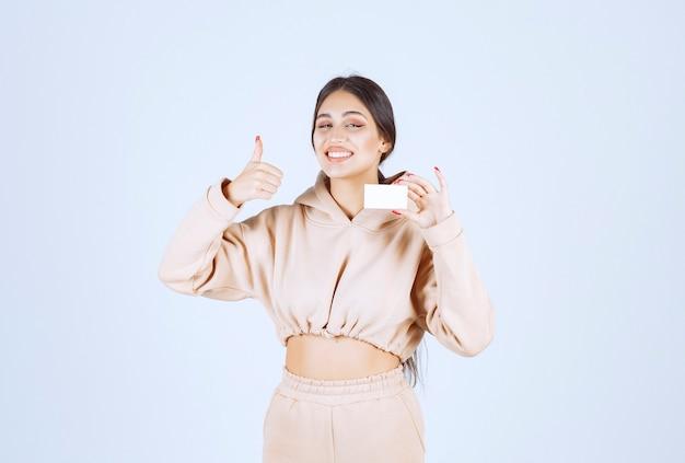 Jeune femme présentant sa carte de visite et montrant un bon signe