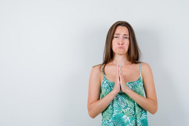 Jeune femme pressant les mains pour demander de l'aide en blouse et l'air offensée, vue de face.