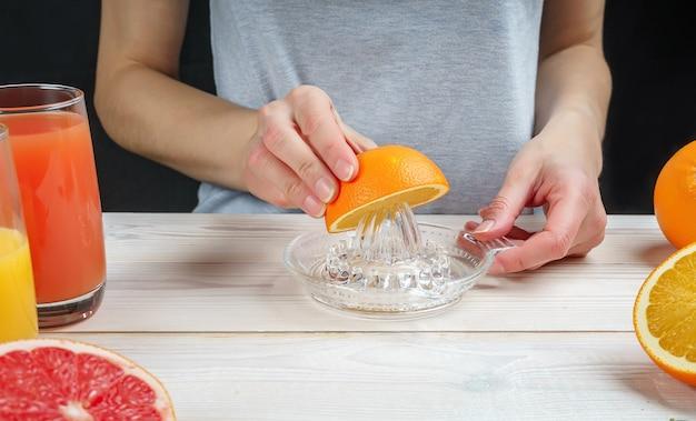 Jeune femme presse le jus d'orange à l'aide d'un presse-agrumes en verre manuel