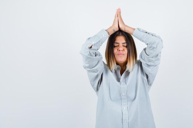 Une jeune femme presse les mains au-dessus de la tête en chemise surdimensionnée et a l'air paisible. vue de face.