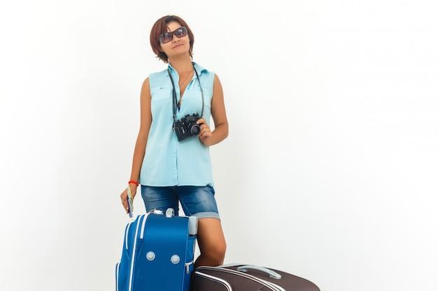 Jeune femme prête à passer ses vacances avec caméra, carte en papier et valise.