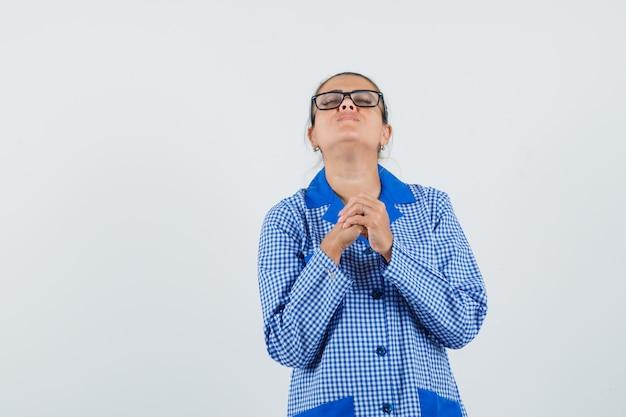 Jeune femme priant en chemise de pyjama vichy bleu et lunettes et à la recherche concentrée. vue de face.
