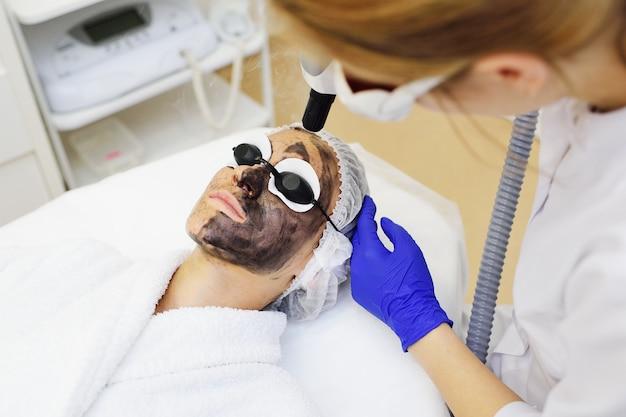 Une jeune femme sur la procédure de peeling au carbone sur le fond de la salle de cosmétologie moderne.
