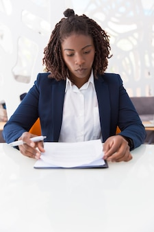 Jeune femme professionnel vérifiant le document
