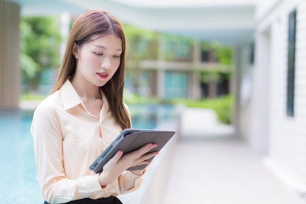 Une jeune femme professionnelle asiatique utilise une tablette pour rechercher des données dans le concept de travail de n'importe où.