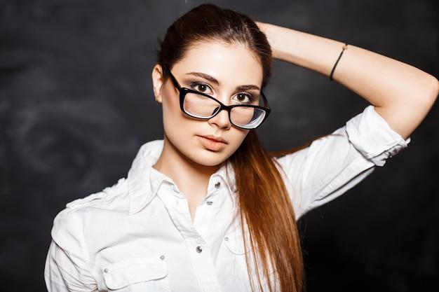 Jeune femme professionnelle à la mode dans des verres et un chemisier blanc