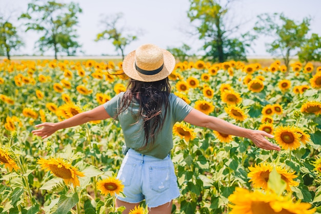 Jeune femme profitant de la nature sur le champ de tournesols.