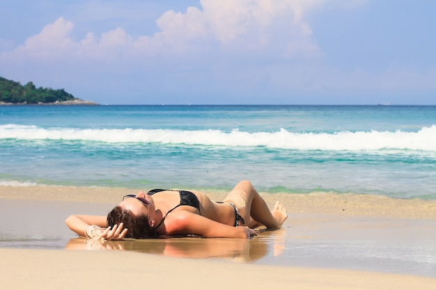 Jeune femme profitant des vacances d'été sur la plage blanche tropicale