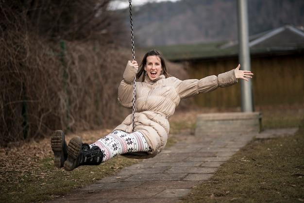 Jeune femme profitant de la vie s'amusant à l'extérieur dans un parc sur une balançoire en riant de plaisir alors qu'elle vole dans les airs avec un bras grand ouvert.