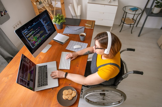 Jeune femme programmeur en fauteuil roulant à la recherche de données sur l'écran de l'ordinateur portable alors qu'il était assis par un bureau dans l'environnement domestique et le développement de logiciels