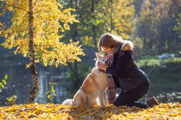 Jeune femme en promenade avec sa race de chien akita inu
