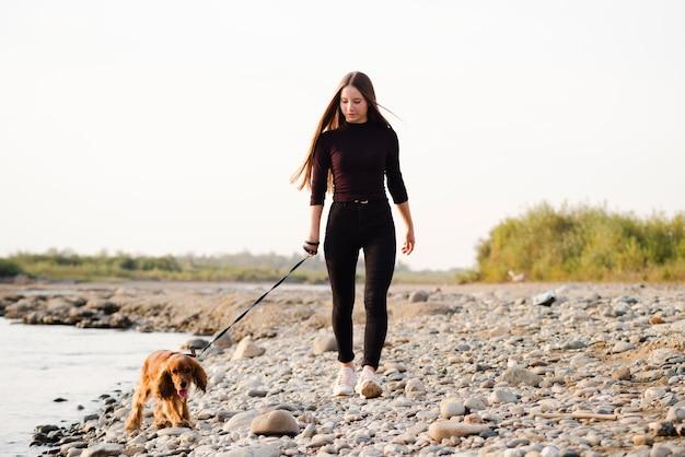 Jeune femme promenant son chien en plein air