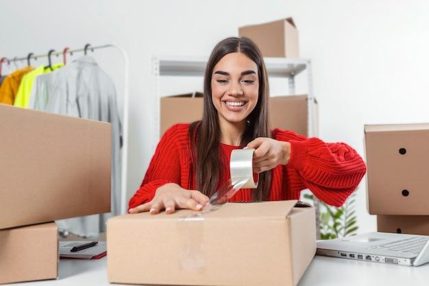 Jeune femme, propriétaire d'une petite entreprise emballant le produit dans des boîtes, le préparant pour la livraison. paquet d'emballage de femmes avec ses produits qu'elle vend en ligne