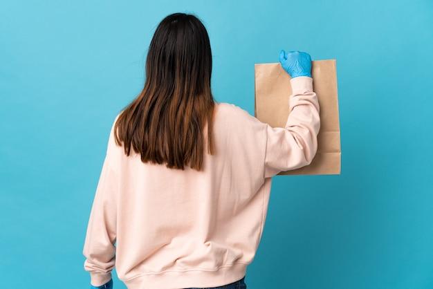 Jeune femme protégeant du coronavirus avec un masque et tenant un sac d'épicerie isolé sur bleu en position arrière