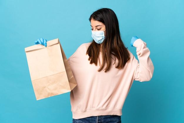 Jeune femme protégeant du coronavirus avec un masque et tenant un sac d'épicerie isolé sur fond bleu célébrant une victoire