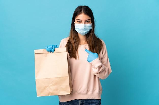 Jeune femme protégeant du coronavirus avec un masque et tenant un sac d'épicerie isolé sur un mur bleu avec une expression faciale surprise