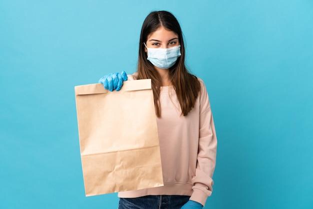 Jeune femme protégeant du coronavirus avec un masque et tenant un sac d'épicerie isolé sur un mur bleu avec une expression heureuse