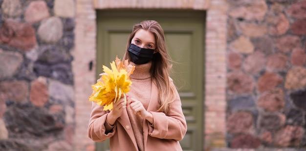 Une jeune femme protégeant du virus corona en marchant dans le parc.