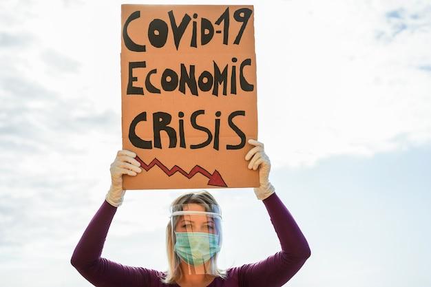 Jeune femme protestant contre la crise économique de covid-19 portant