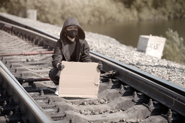 Une jeune femme protestante est assise sur le chemin de fer et regarde la caméra