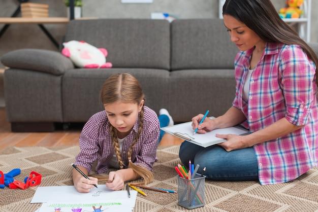 Jeune femme psychologue prenant des notes pendant que la fille dessinait sur du papier blanc