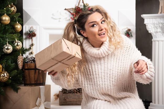 Une jeune femme en pull blanc montrant deux boîtes de cadeaux de noël.
