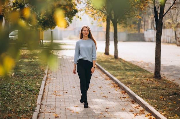 Jeune femme en pull bleu en automne parc