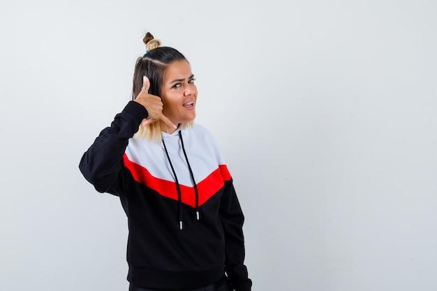 Jeune femme en pull à capuche montrant le geste du téléphone et à la gaieté