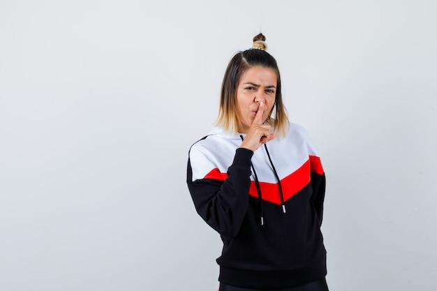 Jeune femme en pull à capuche montrant un geste de silence et l'air confiant