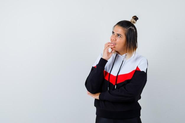 Jeune femme en pull à capuche se rongeant les ongles et ayant l'air concentré
