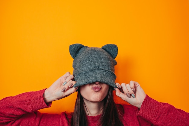 Jeune femme en pull et chapeau à oreilles. vêtements d'hiver. chapeau sur le visage.