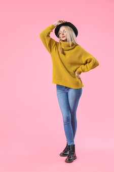 Jeune femme en pull chaud sur la surface de couleur