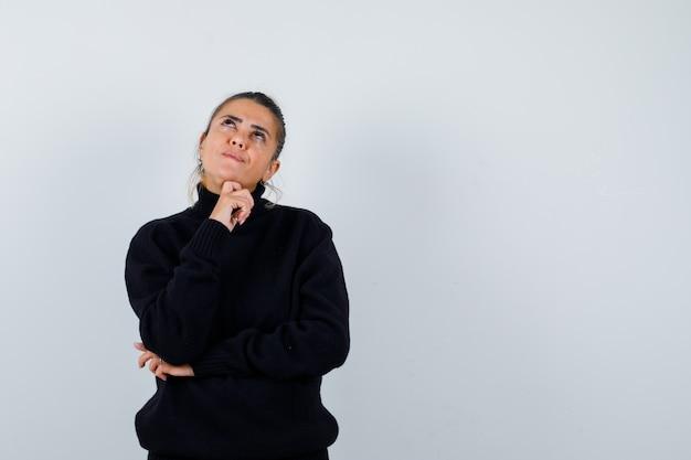 Jeune femme en pull à col roulé noir debout dans la pose de la pensée et à la pensif, vue de face.