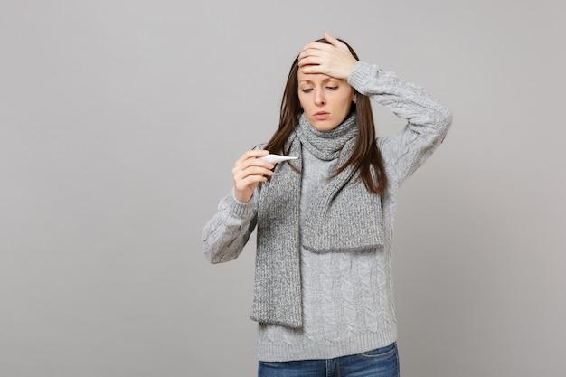 Jeune femme en pull gris, foulard mis la main sur le front en regardant sur le thermomètre isolé sur fond gris. mode de vie sain, traitement des maladies malades, concept de saison froide. maquette de l'espace de copie.