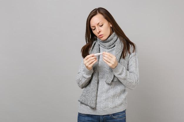 Jeune femme en pull gris, foulard tenant, regardant sur thermomètre isolé sur fond de mur gris en studio. mode de vie sain, traitement des maladies malades, concept de saison froide. maquette de l'espace de copie.