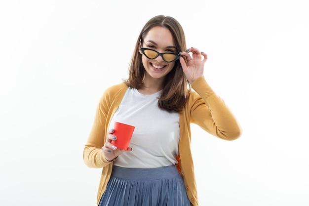 Jeune femme un pull jaune boit du café dans une tasse rouge