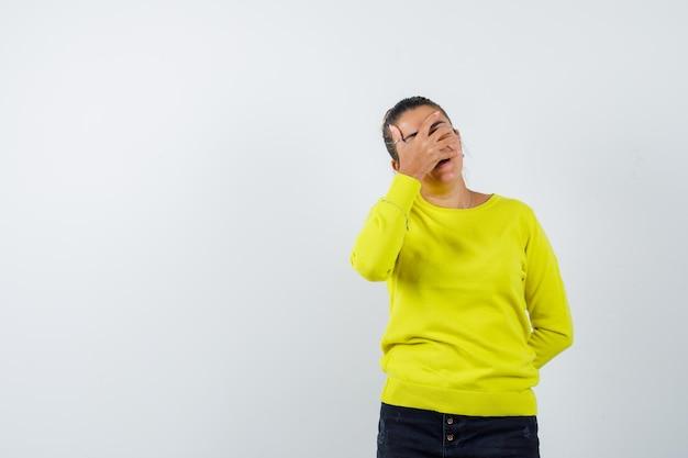 Jeune femme en pull jaune et pantalon noir couvrant le visage avec la main et l'air harcelé
