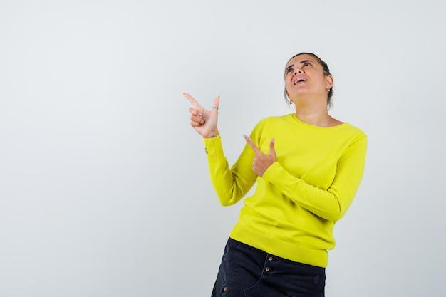 Jeune femme en pull jaune et pantalon noir pointant vers le haut, regardant au-dessus et ayant l'air heureux