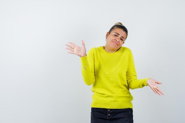 Jeune femme en pull jaune et pantalon noir s'étendant les mains de manière interrogative et à la perplexité