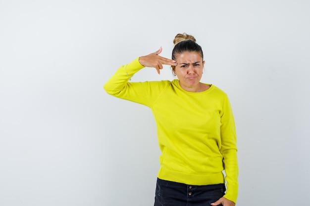Jeune femme en pull, jupe en jean se tirant avec une arme de poing et ayant l'air de s'ennuyer